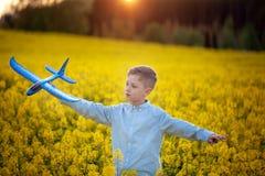 Barnlekar med ett leksakflygplan i solnedg?ngen och dr?mmarna av resan i sommardag royaltyfria foton