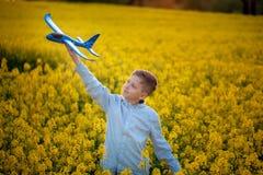 Barnlekar med ett leksakflygplan i solnedg?ngen och dr?mmarna av resan i sommardag royaltyfri fotografi