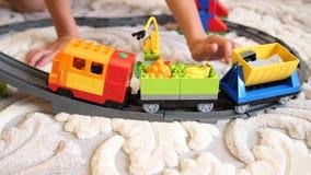 Barnlekarna med leksaker Barn i det modiga rummet som spelar med en byggnadsuppsättning, mot efterkrav objekt från små kuber och lager videofilmer