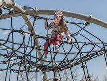 Barnlekarna p? lekplatsen Liten flicka på ett rep arkivfoton