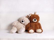 Barnleksaker - björnar av brun och beige färg med guld- liten crownsс sitter på soffan royaltyfria foton