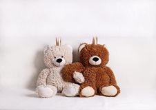 Barnleksaker - björnar av brun och beige färg med guld- liten crownsс sitter på soffan royaltyfri bild