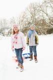 barnliggande som drar den snöig pulkan Royaltyfri Foto