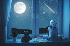 Barnliten flicka på fönstret som drömmer och beundrar stjärnklar himmel på Arkivfoton