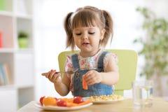 Barnliten flicka som äter sunda grönsaker Royaltyfri Foto