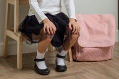 Barnliten flicka som går till skolan som är hemmastadd med ryggsäcksammanträde på stol i hallet nära ytterdörren arkivfoton