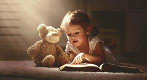Barnliten flicka som läser en magisk bok i mörkerhem Arkivfoton
