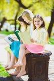 Barnläseböcker på parkerar Flickor som sitter mot träd, och utomhus- sjö Arkivfoton