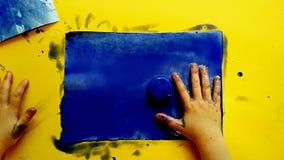 Barnmålning med blå vattenfärgmålarfärg på en gul tabell på skola - konstaktivitet arkivfoton