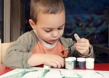 Barnmålning med borsten Arkivfoto