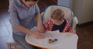 Barnmålning med händer och modern undervisar Little Boy för att dra lager videofilmer