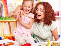 Barnmålning på stafflin. Royaltyfri Foto