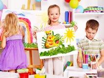 Barnmålning på stafflin. Arkivfoto