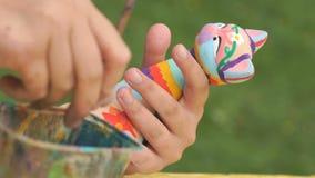 Barnmålningborstar på leran figurerar utomhus stock video