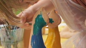 Barnmålningborstar på leran figurerar utomhus arkivfilmer