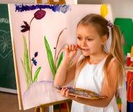 Barnmålningfinger på staffli Grupp av ungar med läraren royaltyfri bild
