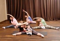 Barnmödrar och deras behandla som ett barn göra yogaövningar på filtar på konditionstudion Arkivbild