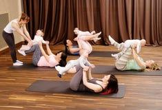 Barnmödrar och deras behandla som ett barn göra yogaövningar på filtar på konditionstudion Royaltyfria Bilder