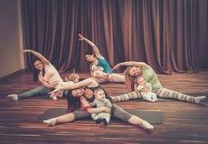 Barnmödrar och deras behandla som ett barn göra yogaövningar på filtar på konditionstudion Arkivfoton