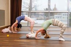 Barnmödrar och deras behandla som ett barn göra yogaövningar på filtar på konditionstudion Royaltyfri Bild