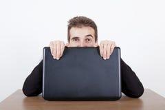 Dölja bak en bärbar dator Royaltyfri Bild