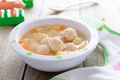 Barnmat: soppa med potatisar och hönaköttbullar arkivbild
