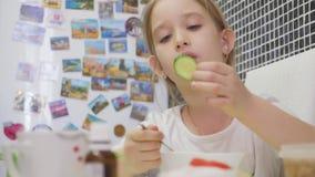 barnmatställen som äter flickan, har home little soup Lilla flickan har en matställe arkivfilmer