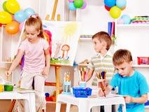 Barnmålning på stafflin. Arkivbild