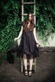 Barnmodekvinnan i svart elegant klänning lutar på trästege royaltyfri bild