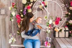 Barnmoder som rymmer hennes nyfödda barn Mammasjukvård behandla som ett barn Kvinna och nyfödd pojke i rummet Moder som spelar me Royaltyfri Bild