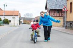 Barnmoder som undervisar henne 3 år gammal liten son för att rida en cykel royaltyfria bilder