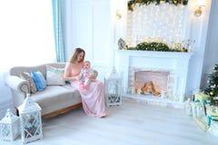 Barnmoderinnehavet behandla som ett barn och sammanträde på soffan nära lyktor, spisen och julgranen fotografering för bildbyråer