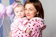 Barnmodern kramar hennes lilla dotter i rummet royaltyfria foton