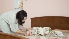 Barnmodern kysser i panna hennes lilla dotter under henne ` s som sover på säng lager videofilmer