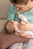 Barnmodern som ammar henne, behandla som ett barn hemma Royaltyfri Fotografi