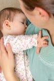 Barnmodern som ammar henne, behandla som ett barn hemma Royaltyfri Bild