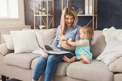 Barnmodern som arbetar och spenderar tid med, behandla som ett barn arkivfoton