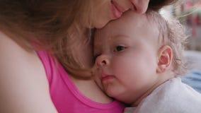 Barnmodern som rymmer henne, behandla som ett barn i hennes armar arkivfilmer