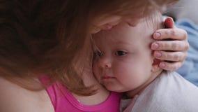 Barnmodern som rymmer henne, behandla som ett barn i hennes armar stock video