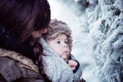 Barnmodern som rymmer hennes nyfött, behandla som ett barn i vinter arkivbild