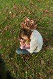 Barnmodersammanträde i gräs i en parkera, medan kyssa henne behandla som ett barn G Royaltyfria Foton