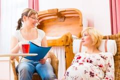 Barnmorska som i praktiken ser den gravida modern Arkivfoto