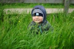 Barnnederlag i gräset Arkivbild