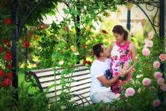 Barnpar bland blommorna av rosor Fotografering för Bildbyråer