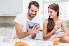 Barnpar genom att använda minnestavlan på frukosten Arkivbilder