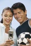Barnpar genom att använda mobiltelefonen med fotbollbollen Arkivbild