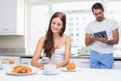 Barnpar genom att använda teknologi på frukosten Royaltyfria Foton