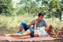 Barnpar har en vila på picknicken som rymmer händer Royaltyfri Fotografi
