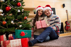 Barnpar i julhattar som rymmer gåvor arkivfoto