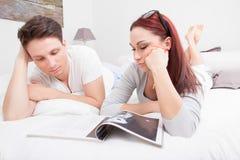 Barnpar i läs- tidskrift för säng tillsammans arkivfoto